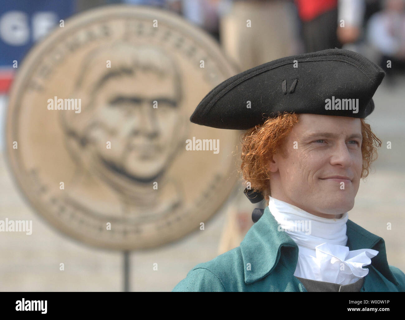 A Thomas Jefferson impersonator stands next to a model of