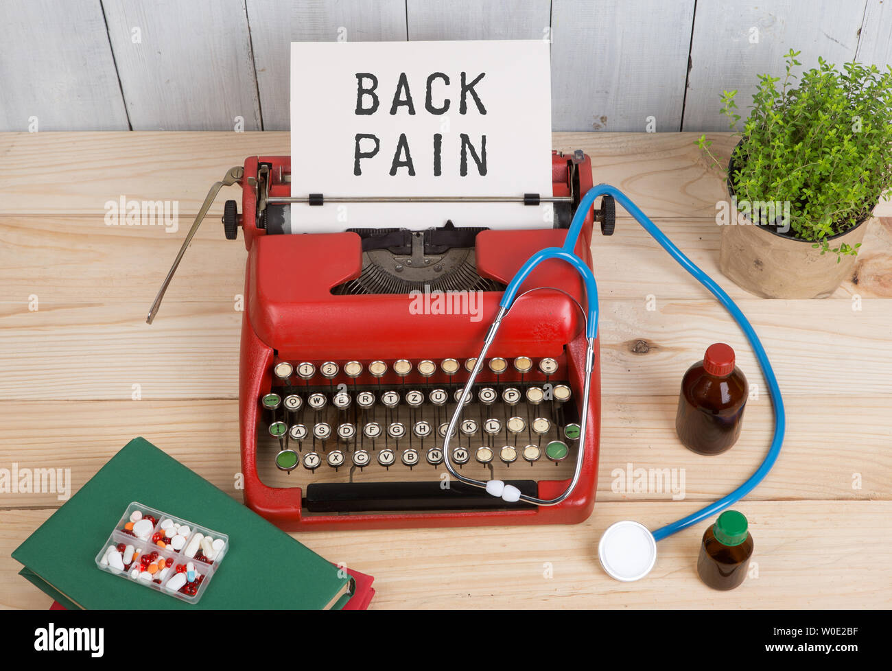 Prescription medicine or medical diagnosis - doctor workplace with stethoscope, pills, typewriter with text Back Pain on wooden table - Stock Image