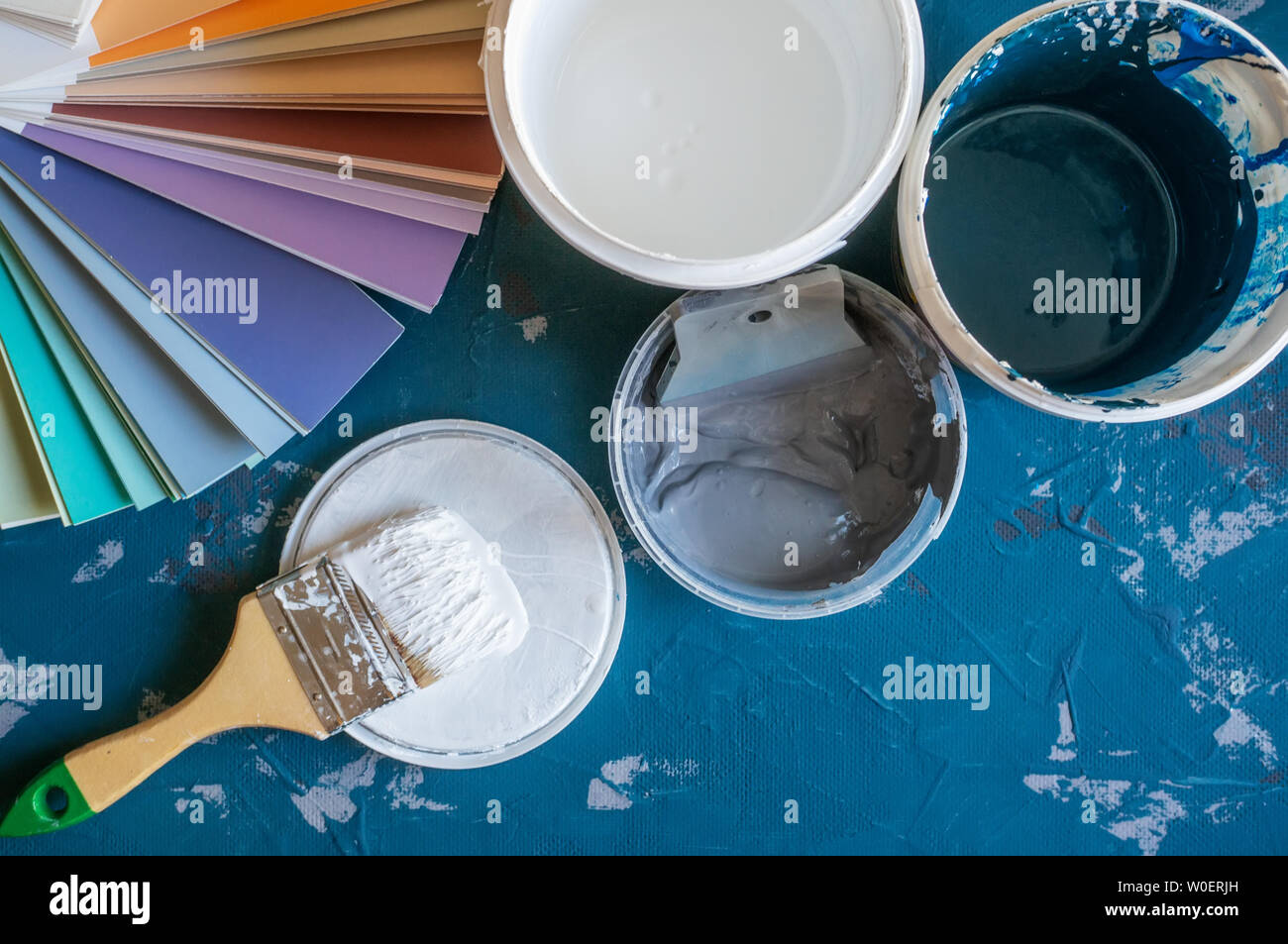 Choose a paint color for the walls. Spatula for painting and wall putty and background in a tray next to a bucket of putty.. Create a background - Stock Image