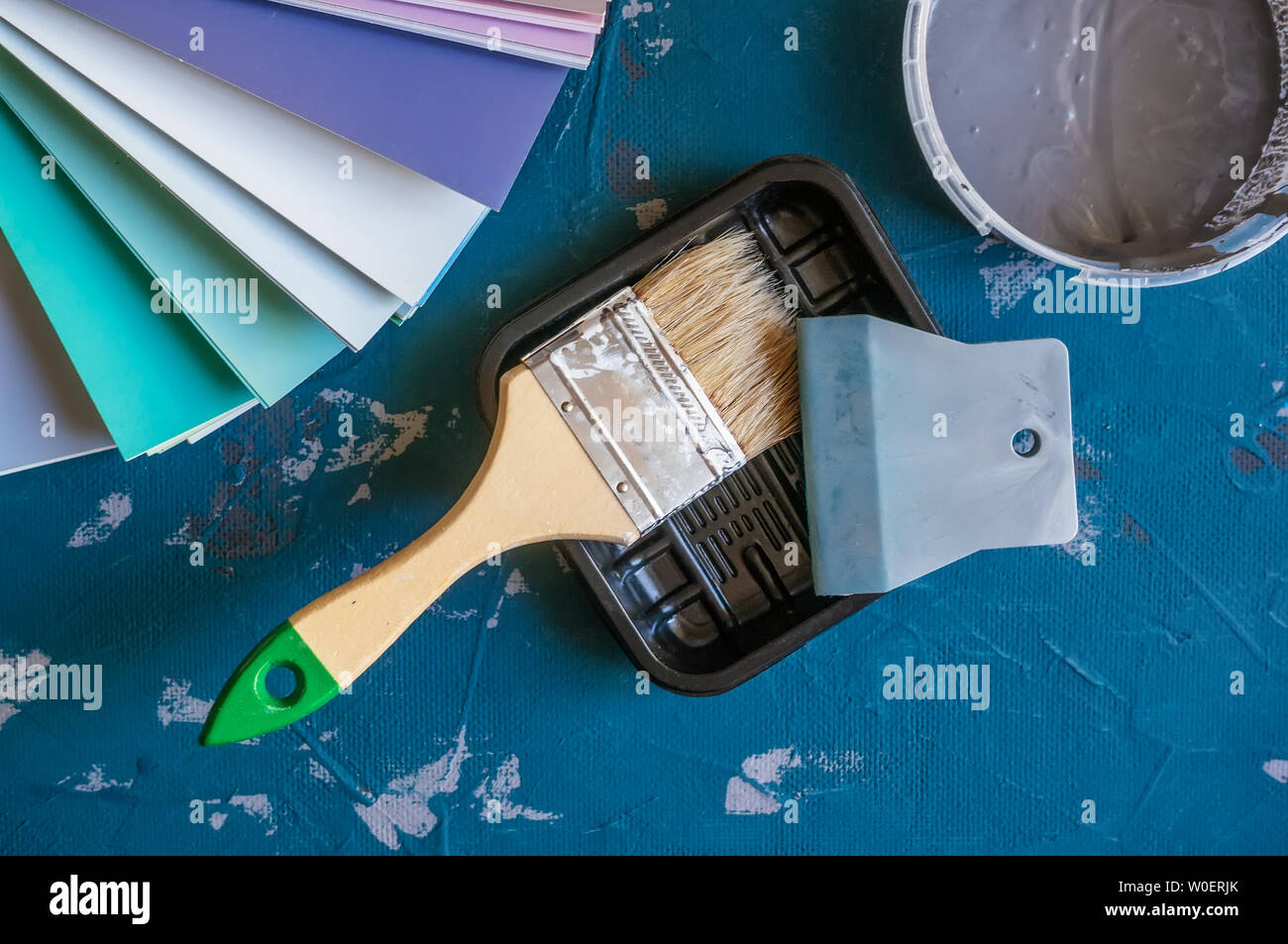 Choose a paint color for the walls. Spatula for painting and wall putty and background in a tray next to a bucket of putty - Stock Image