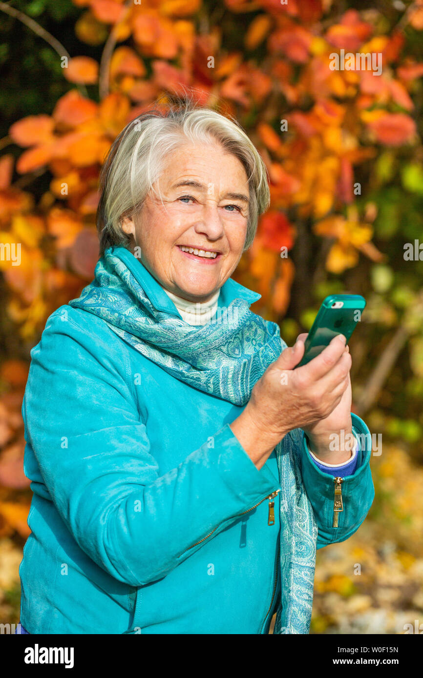 Sunny portrait of a smilling pretty senior woman with his phone in front of a tree with autumnal colors. - Stock Image