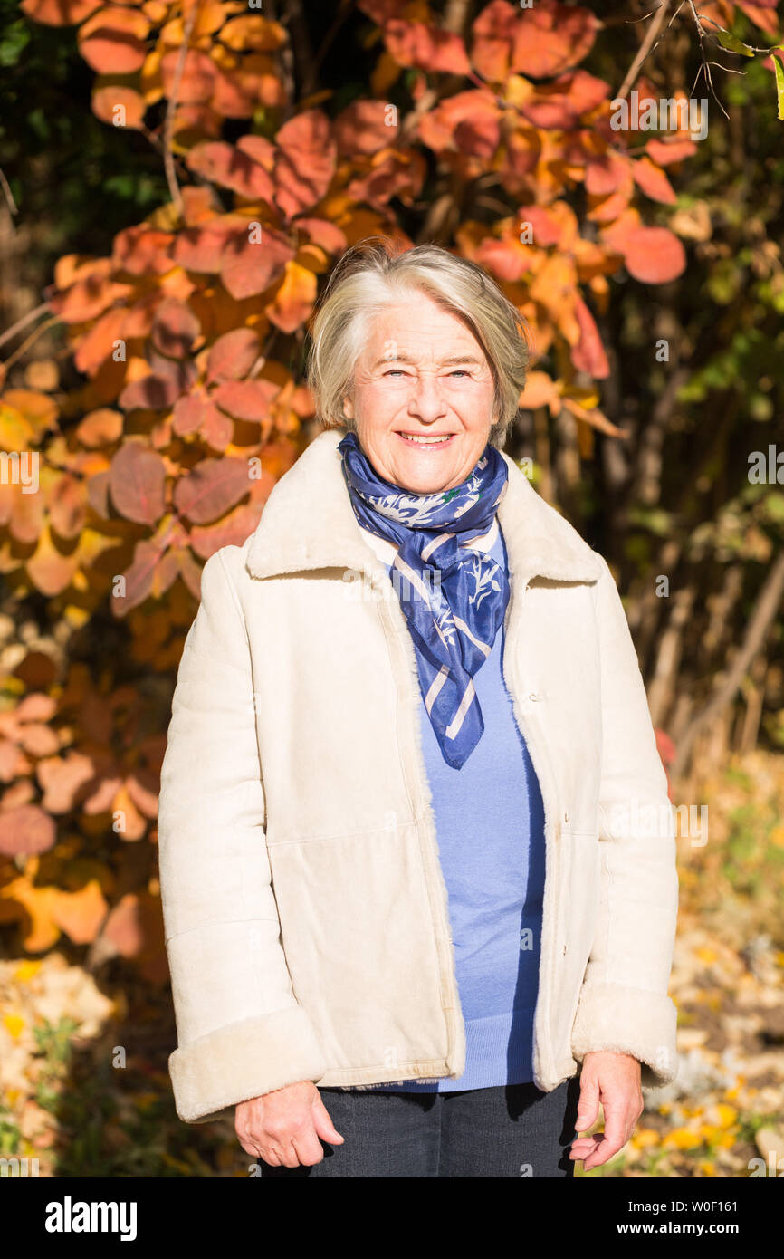 Sunny portrait of a pretty senior woman in front of a tree with autumnal colors. - Stock Image