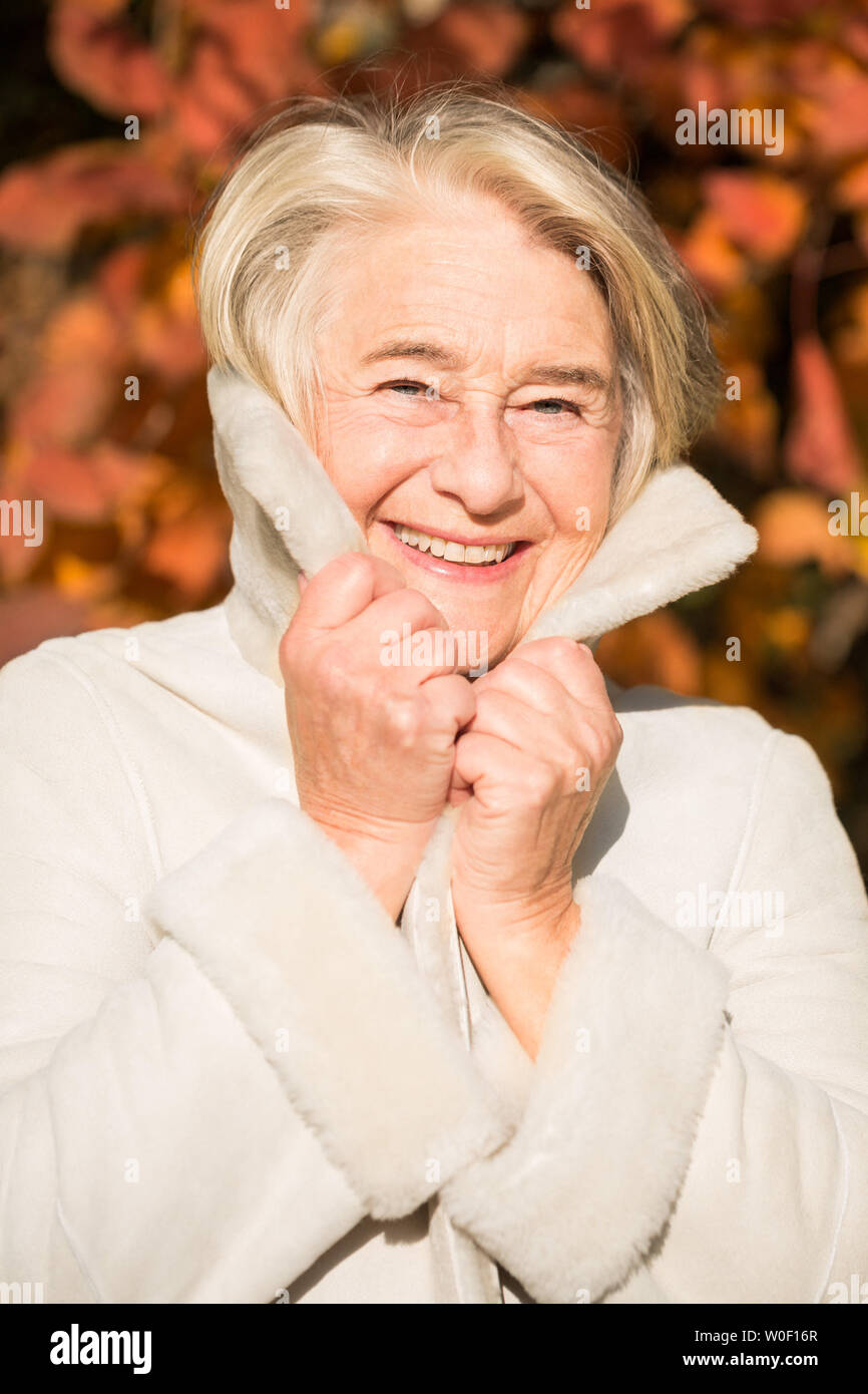 Sunny portrait of a smiling grandma holding his coat collar with his hands in nature in autumnal colors. - Stock Image