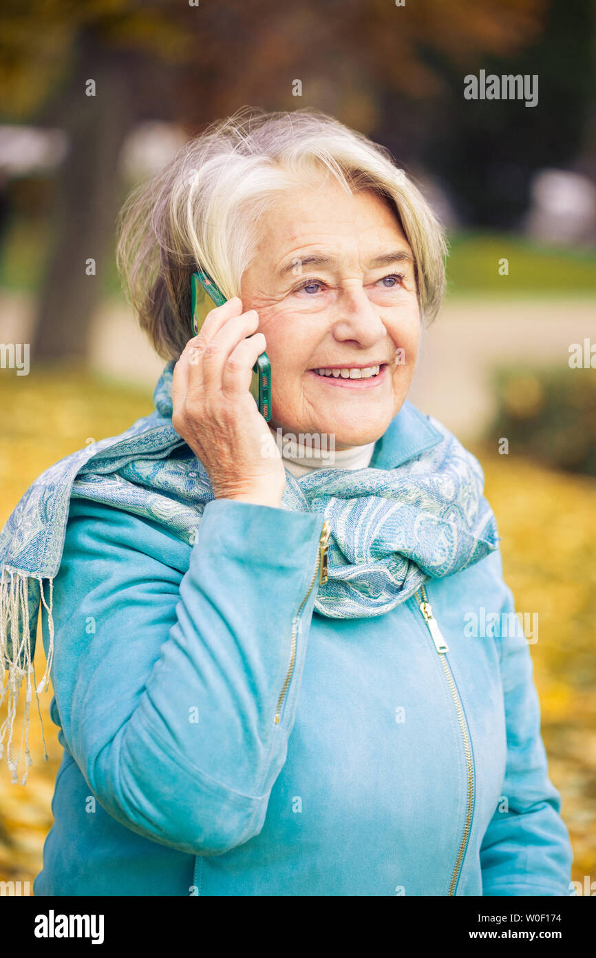 Sunny portrait of a smilling pretty senior woman calling with his phone in front of a tree with autumnal colors. - Stock Image