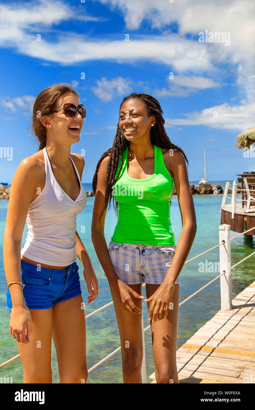2 smiling girlfriends posing on a footbridge coming from a bar on stilts on a Caribbean beach in a paradisiacal landscape. - Stock Image