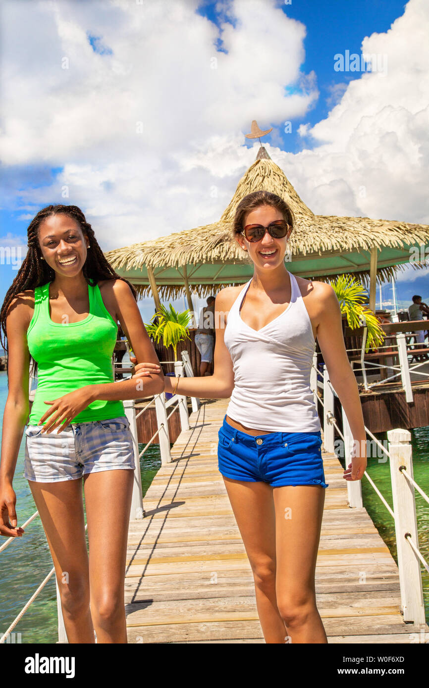 2 smiling girlfriends walking on a footbridge coming from a bar on stilts on a Caribbean beach in a paradisiacal landscape. - Stock Image