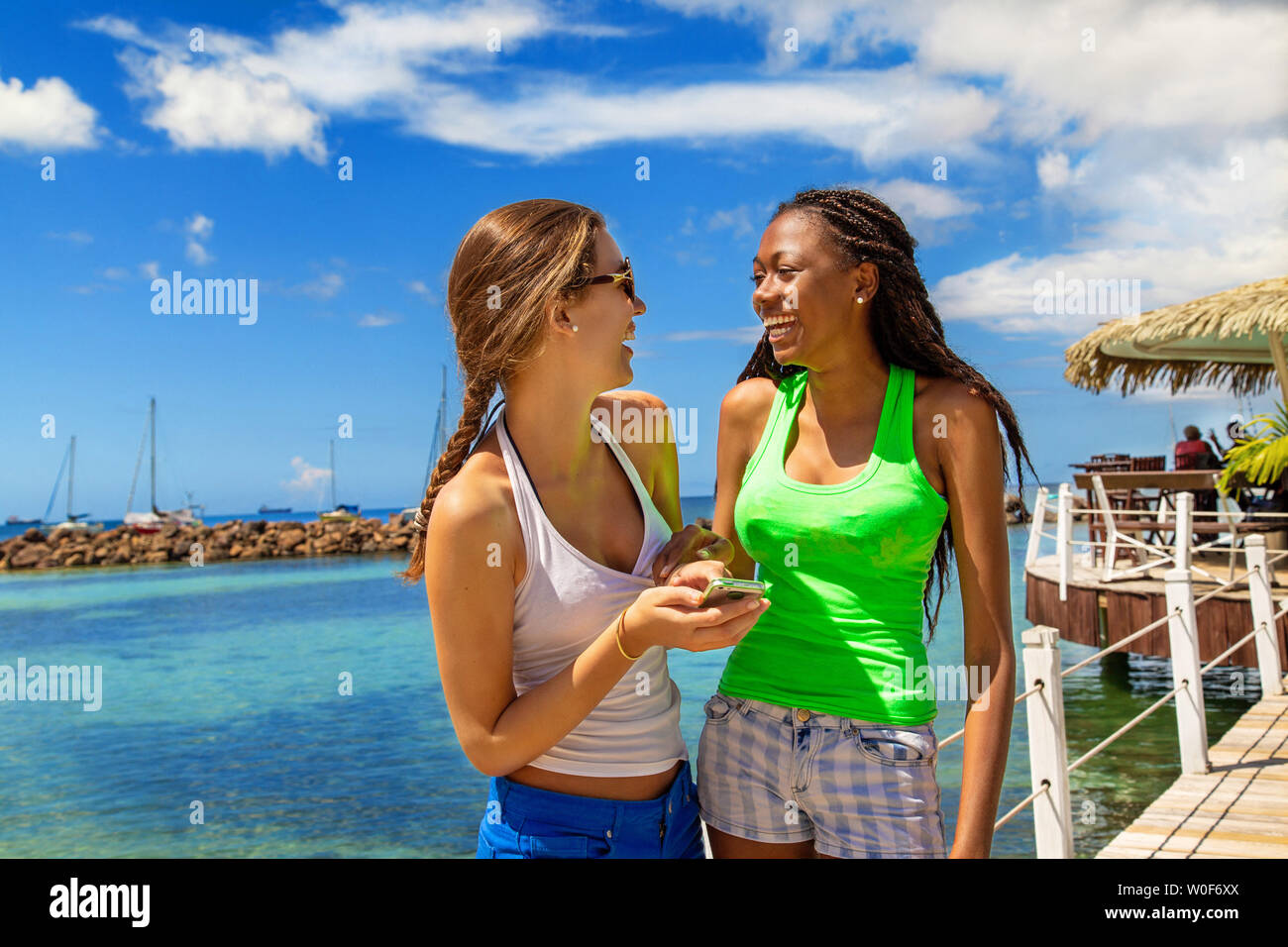 2 smiling girlfriends speaking and smiling  on a footbridge coming from a bar on stilts on a Caribbean beach in a paradisiacal landscape. - Stock Image
