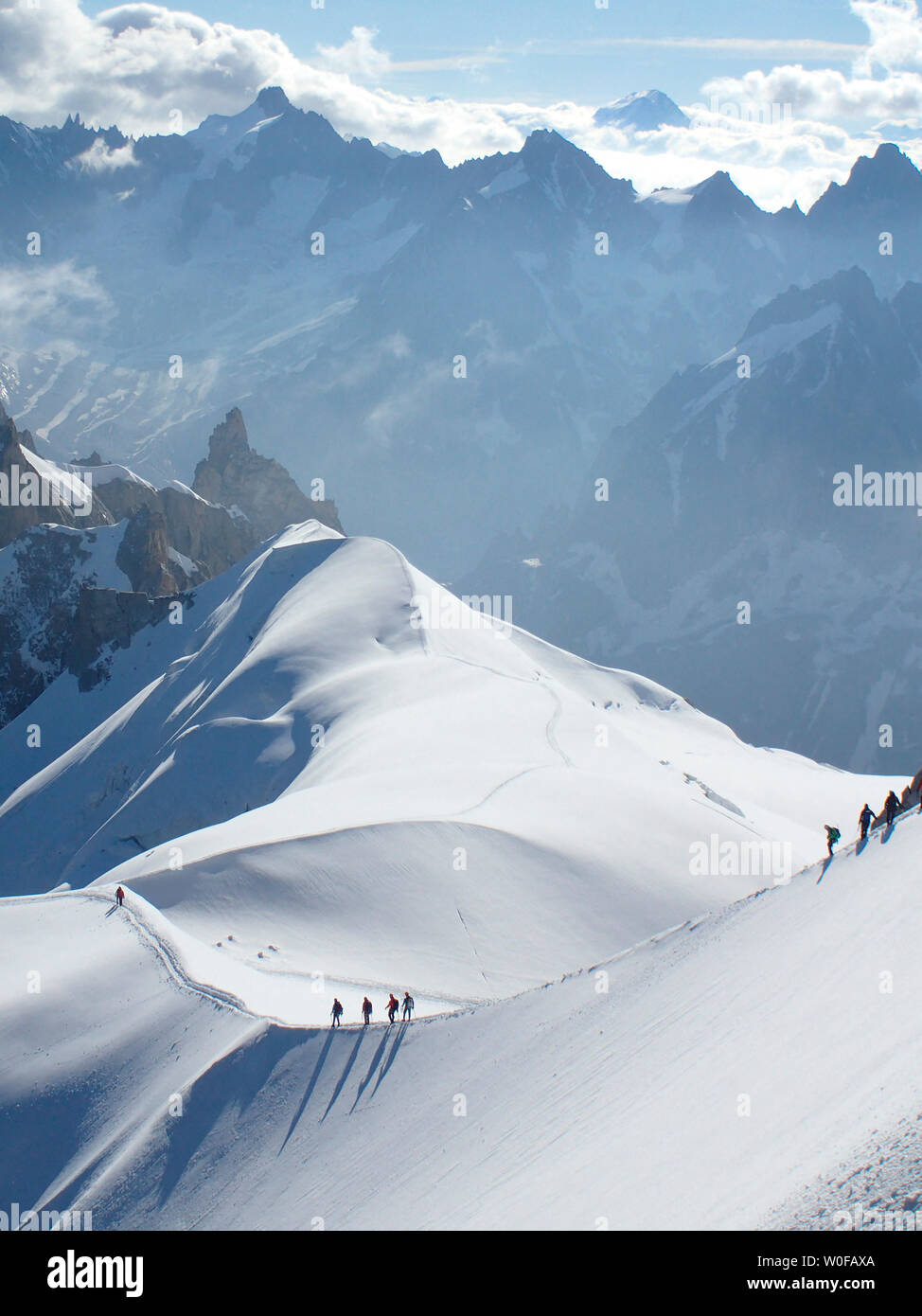 France, haute savoy, Chamonix, Mont blanc range, some alpinists are hiking on the snow edge of the aiguille du midi - Stock Image