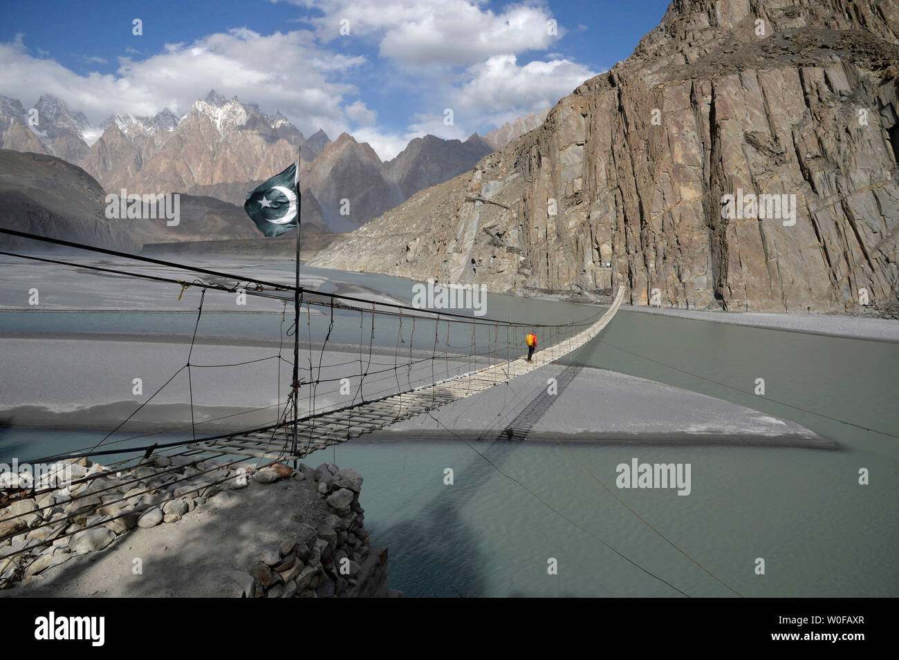 Pakistan, Gilgit Baltistan area, Passu, a man is crossing the Hunza river on the Hosseini suspension bridge in front of the Karakoram mountains - Stock Image