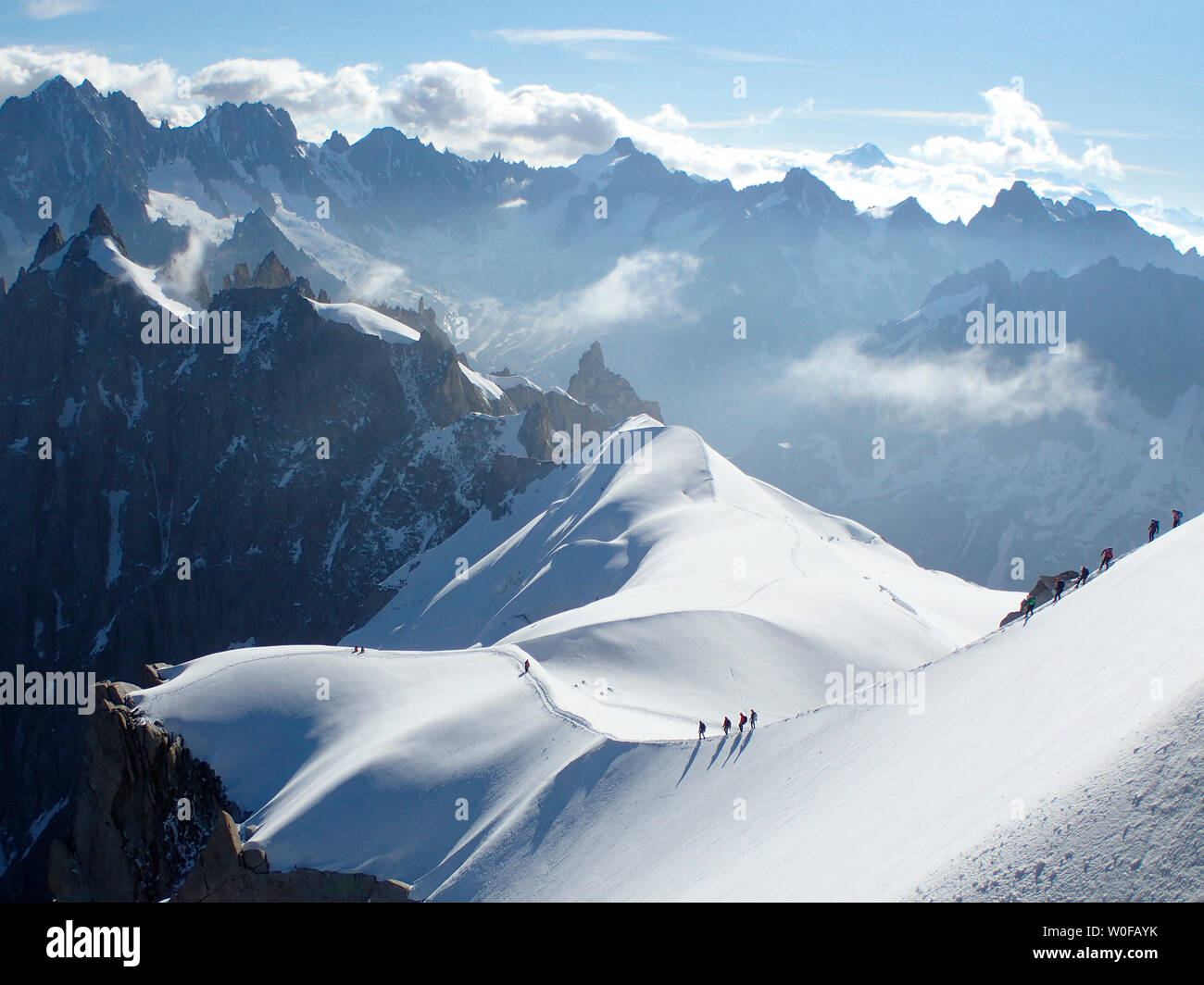France, haute savoy, Chamonix, Mont blanc range, a group of alpinists is hiking on the snow edge of the aiguille du midi - Stock Image