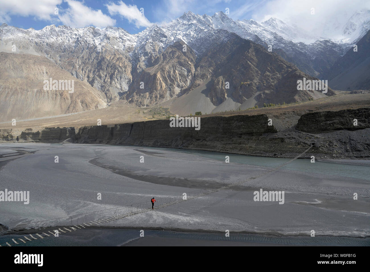 Pakistan, Gilgit Baltista area, Passu, a man is crossing the Hunza river on the Zadabad suspension bridge in front of the Karakoram mountains - Stock Image