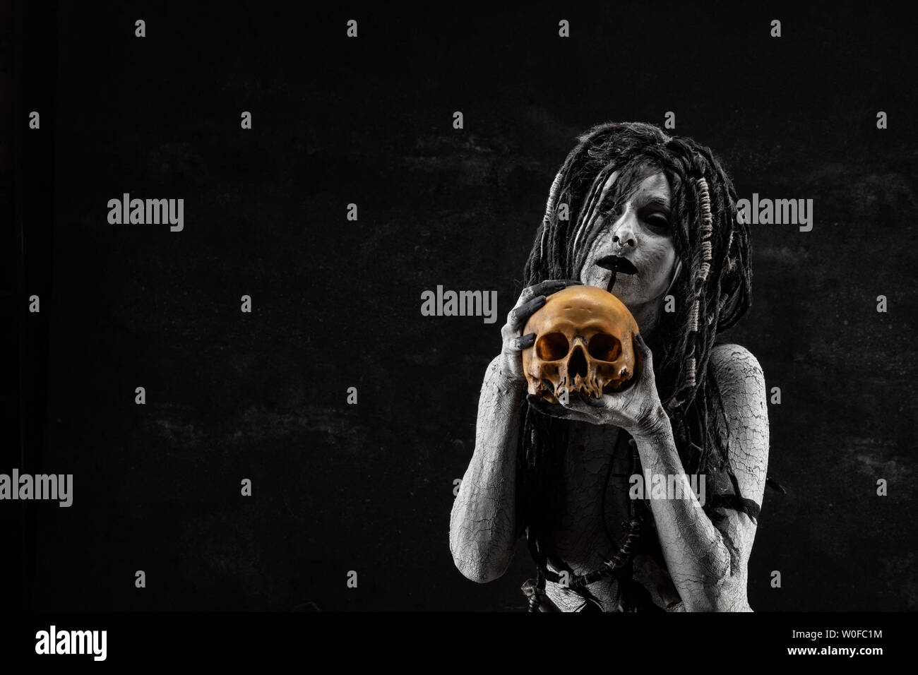 Portrait of a shaman holding a human skull in his hands - Stock Image