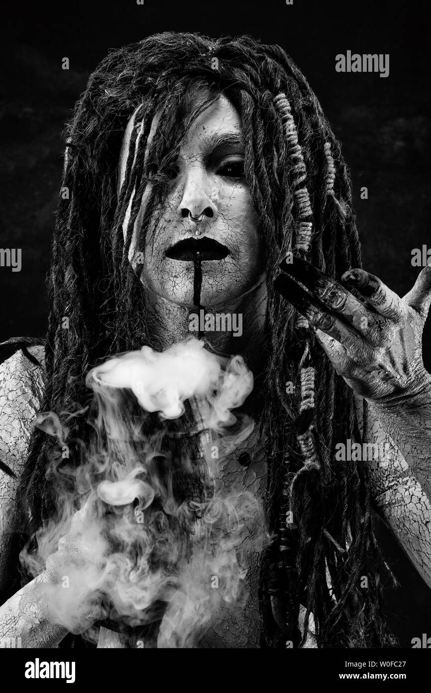 Portrait of a shaman holding a steaming horn - Stock Image