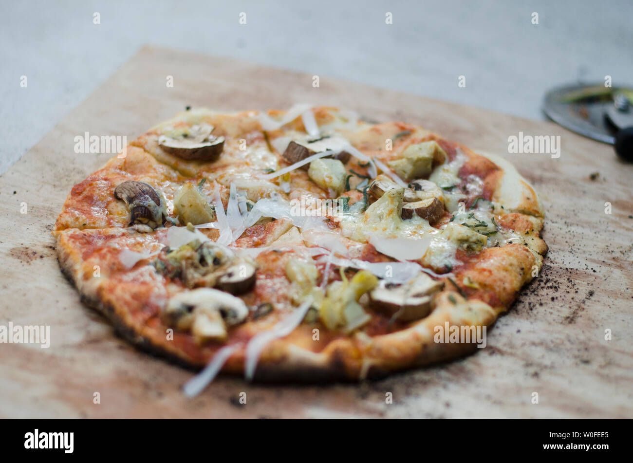 Rustic Pizza On Wooden Slate - Stock Image