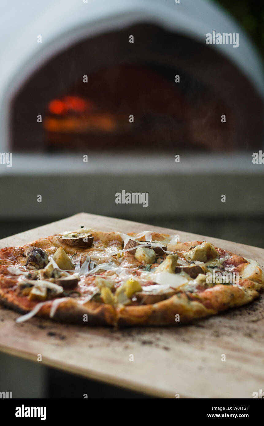Rustic Pizza on Wooden Slate With Oven in Background - Stock Image