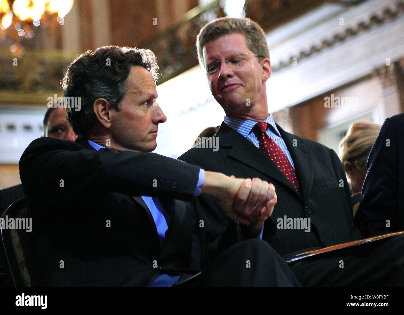 Treasury Secretary Tim Geithner (C) shakes hands with HUD Secretary Shaun Donovan after the two spoke at a conference on the future of housing finance at the Treasury Department in Washington on August 17, 2010.   UPI/Kevin Dietsch Stock Photo