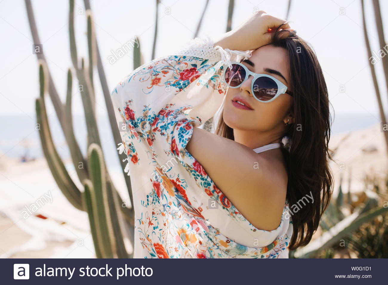 Close-up portrait of cheerful girl in white sunglasses posing with hands up on cactus background. Amazing joyful young woman in attire with floral print having fun outside in summer vacation - Stock Image