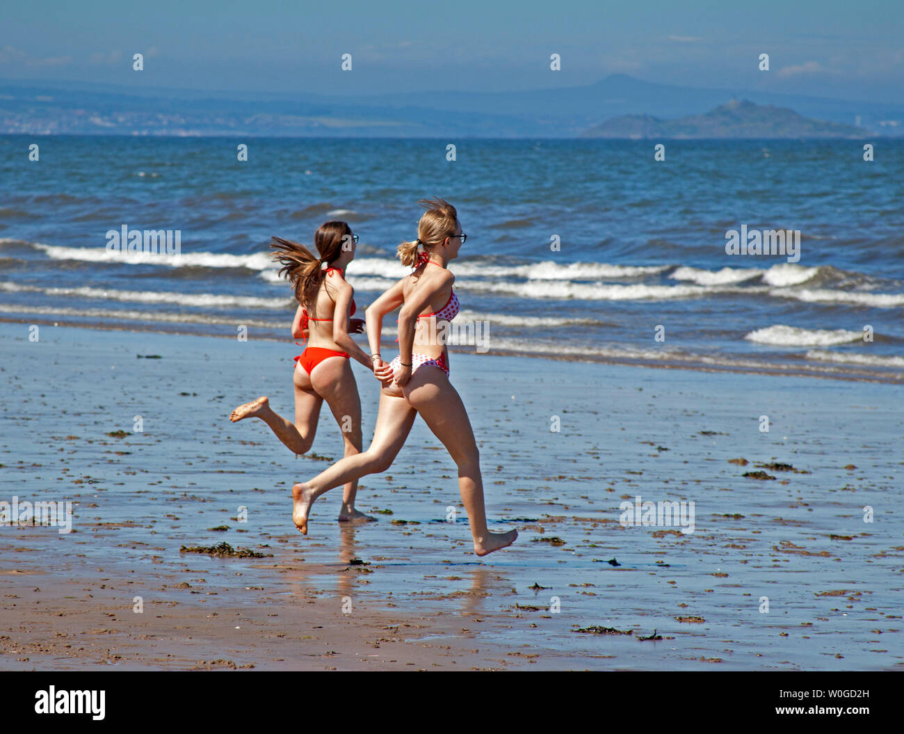 Portobello Beach, Edinburgh, Scotland. 27th June 2019. UK weather. A group of Italian students swap a scorching temperature of 36 degrees in their home city of Milan for an enjoyable hot 19 degrees on Edinburgh's coastline. Also, two girls keep cool by splashing each other by kicking the sea water at each other. - Stock Image