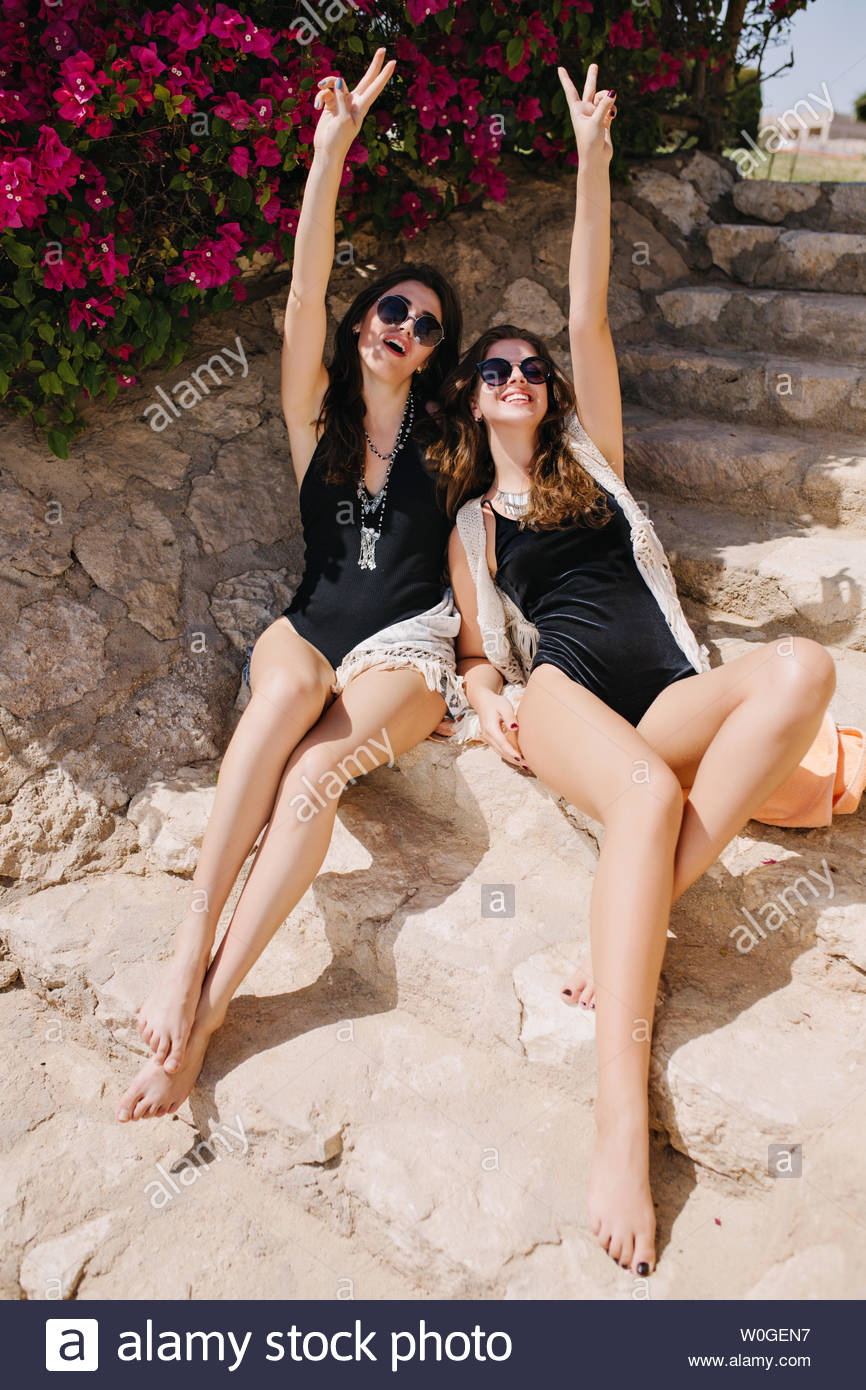 bbea6ca94d Joyful brunette twins sisters having fun, while sitting on stone steps in  exotic country.