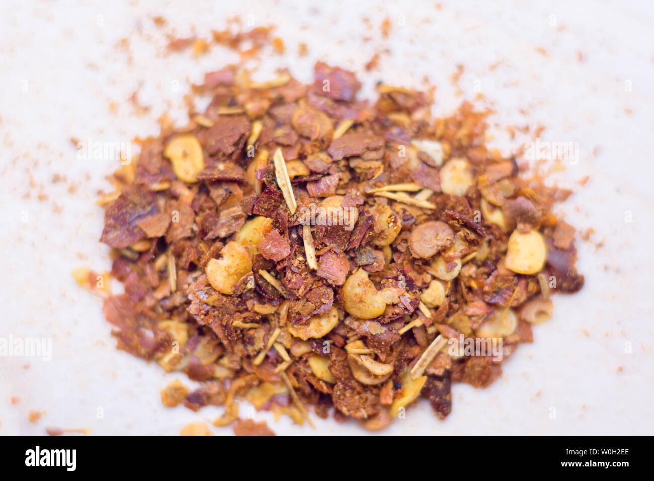 Dried chili flakes and seeds isolated on white background.Pile crushed red cayenne pepper,top view. Stock Photo
