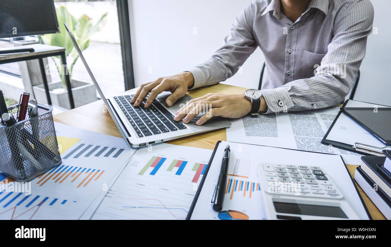 Businessman accountant working audit and calculating expense financial data on graph documents, doing finance in workplace. - Stock Image