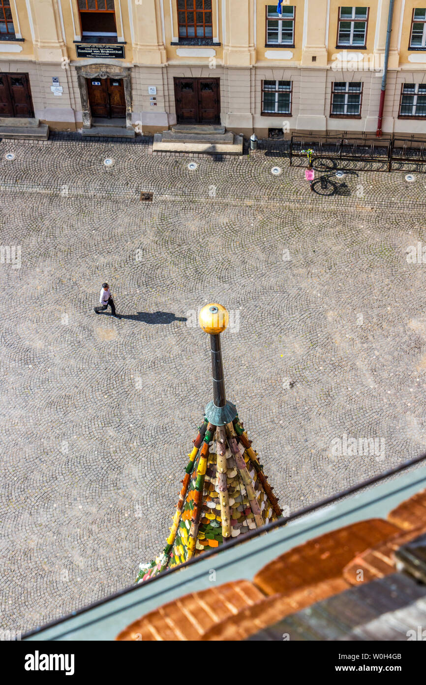 SIBIU, ROMANIA - AUGUST 28, 2017: Unidentified man walks on the Huet Square and his shadow almost touches the top of the turret of Saint Mary Lutheran Stock Photo