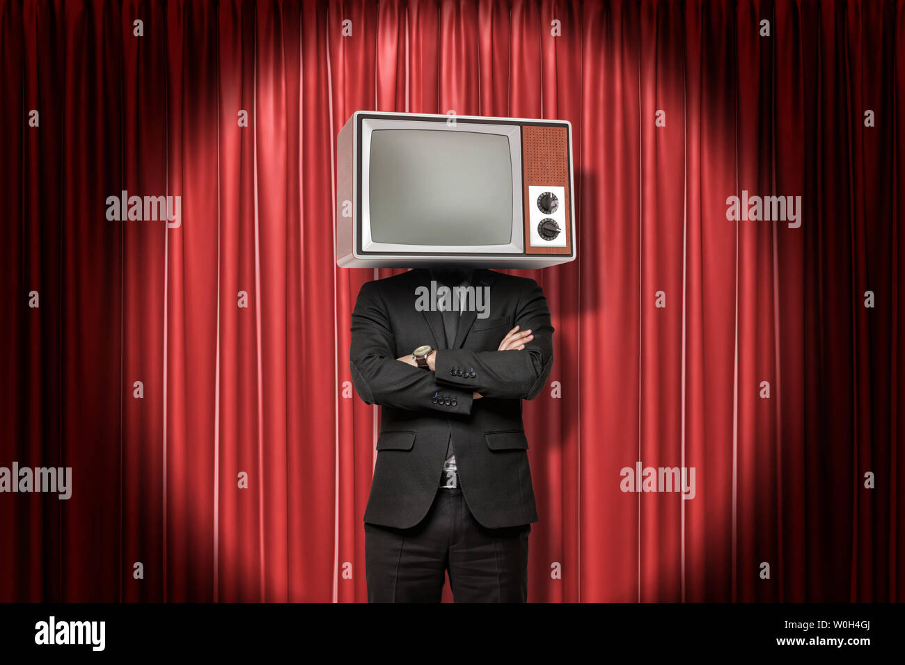 Front crop image of man in suit, with arms folded, and with TV set instead head, standing in spotlight at red stage curtain. Stock Photo