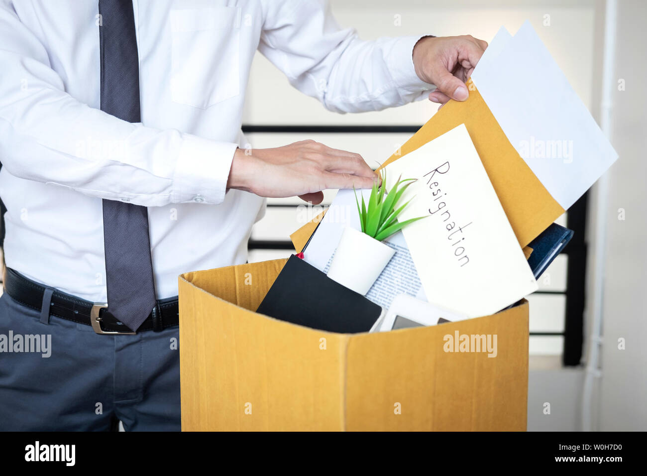 Businessman sending letter will being resignation and carrying packing belongings company and files into brown cardboard box, changing and resigning f - Stock Image