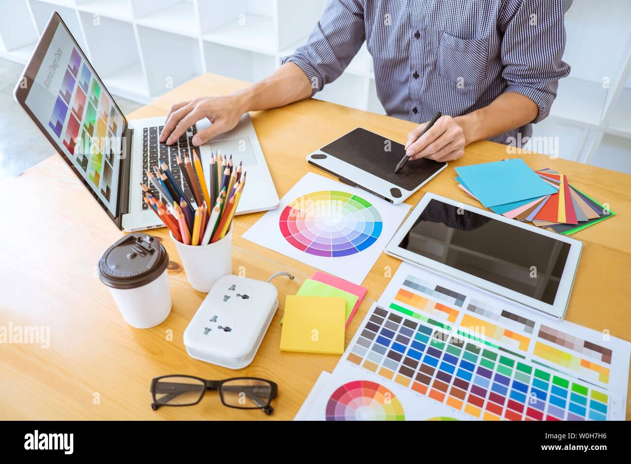 Young creative graphic designer working on project architectural drawing and color swatches, selection coloring on graphic chart with work tools and e Stock Photo
