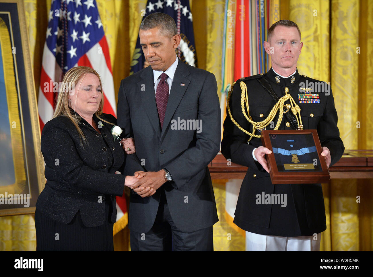President Barack Obama comforts Shyrell Jean Copas who accepted the Medal of Honor on behalf of her father, Specialist Four Ardie R. Copas during a ceremony in the East Room of the White House in Washington on March 18, 2014. Obama awarded the Medal of Honor to 24 veterans, three of whom are still living, who fought in World War II, the Korean War and the Vietnam War. They were previously denied the prestigious honor due to their Hispanic, black or Jewish backgrounds. UPI/Kevin Dietsch - Stock Image