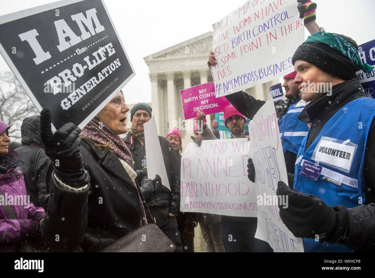 An anti-abortion supporter argues with supporters of women's rights groups as they participate in a rally in front of the Supreme Court as the Court considers two cases brought by Hobby Lobby and Conestoga Wood involving religious objections to the birth control mandate in the Affordable Care Act, in Washington, D.C. on March 25, 2014.  UPI/Kevin Dietsch Stock Photo