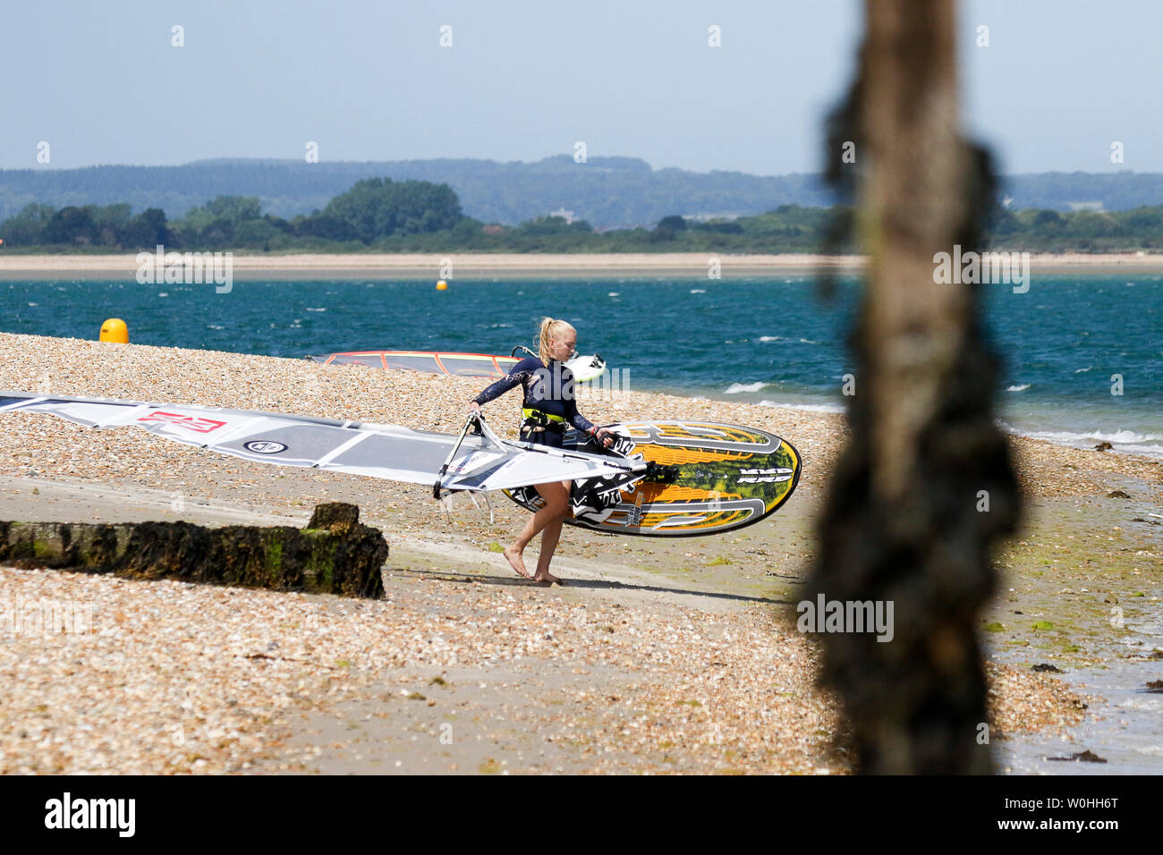 Bracklesham Road, Hayling Island. 27th June 2019. Beautiful sunny and windy weather along the south coast today. Windsurfers enjoying the conditions off Hayling Island Sailing Club in Hampshire. Credit: james jagger/Alamy Live News - Stock Image