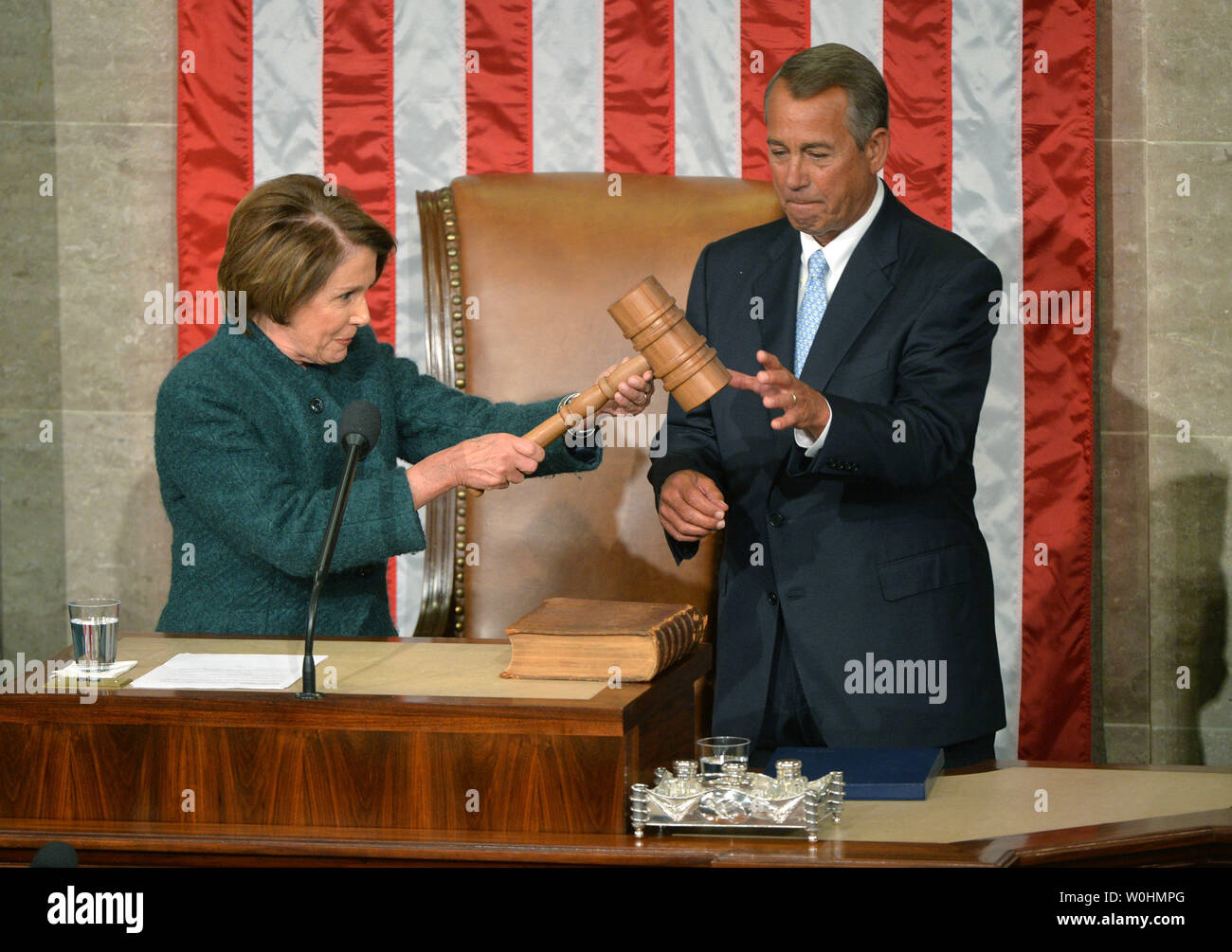 House Minority Leader Nancy Pelosi, D-CA, passes the gavel to Speaker of the House John Boehner, R-OH, after he was reelected as the Speaker during the first day of the 114th Congress, inside the House Chambers of the U.S. Capitol Building in Washington, D.C. on January 6, 2015. Photo by Kevin Dietsch/UPI - Stock Image