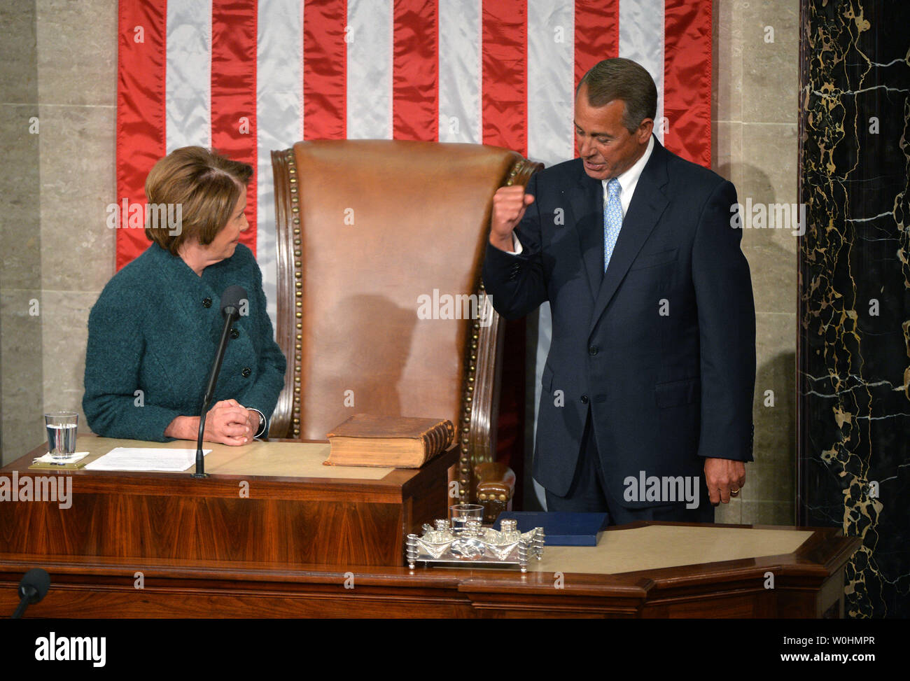 House Minority Leader Nancy Pelosi, D-CA, watches as Speaker of the House John Boehner, R-OH,  pumped his fist as she talks about Ohio State, after he was reelected as the Speaker during the first day of the 114th Congress, inside the House Chambers of the U.S. Capitol Building in Washington, D.C. on January 6, 2015. Photo by Kevin Dietsch/UPI - Stock Image