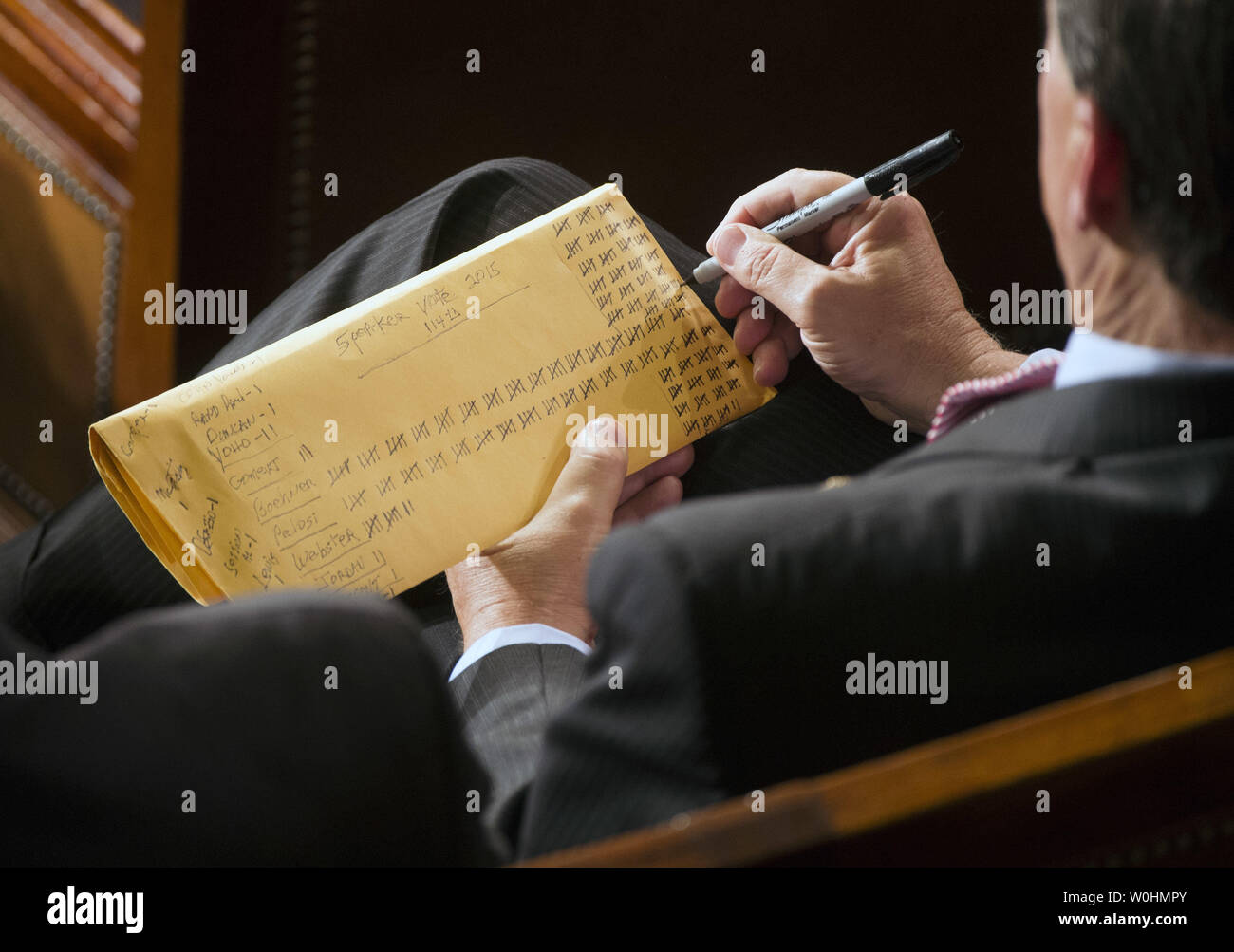 A member of Congress keeps a tally during the election for Speaker of the House during the first day of the 114th Congress, inside the House Chambers of the U.S. Capitol Building in Washington, D.C. on January 6, 2015. Speaker John Boehner, R-OH, retained his position despite a Tea Party challenge. Photo by Kevin Dietsch/UPI - Stock Image
