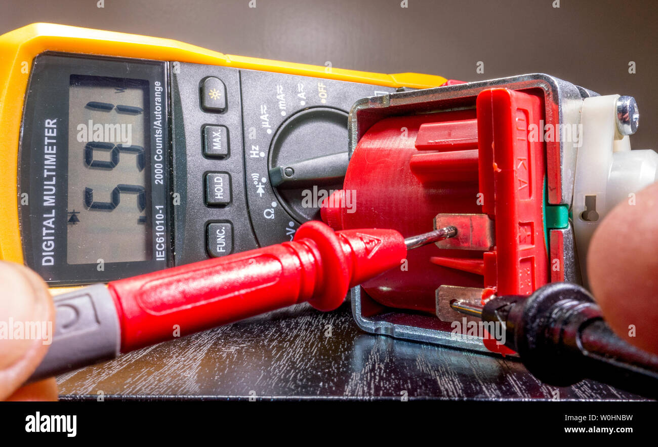 Closeup of an electrician's hands attaching the probes of a digital multimeter to a small motor, to take a reading and check its functionality. - Stock Image