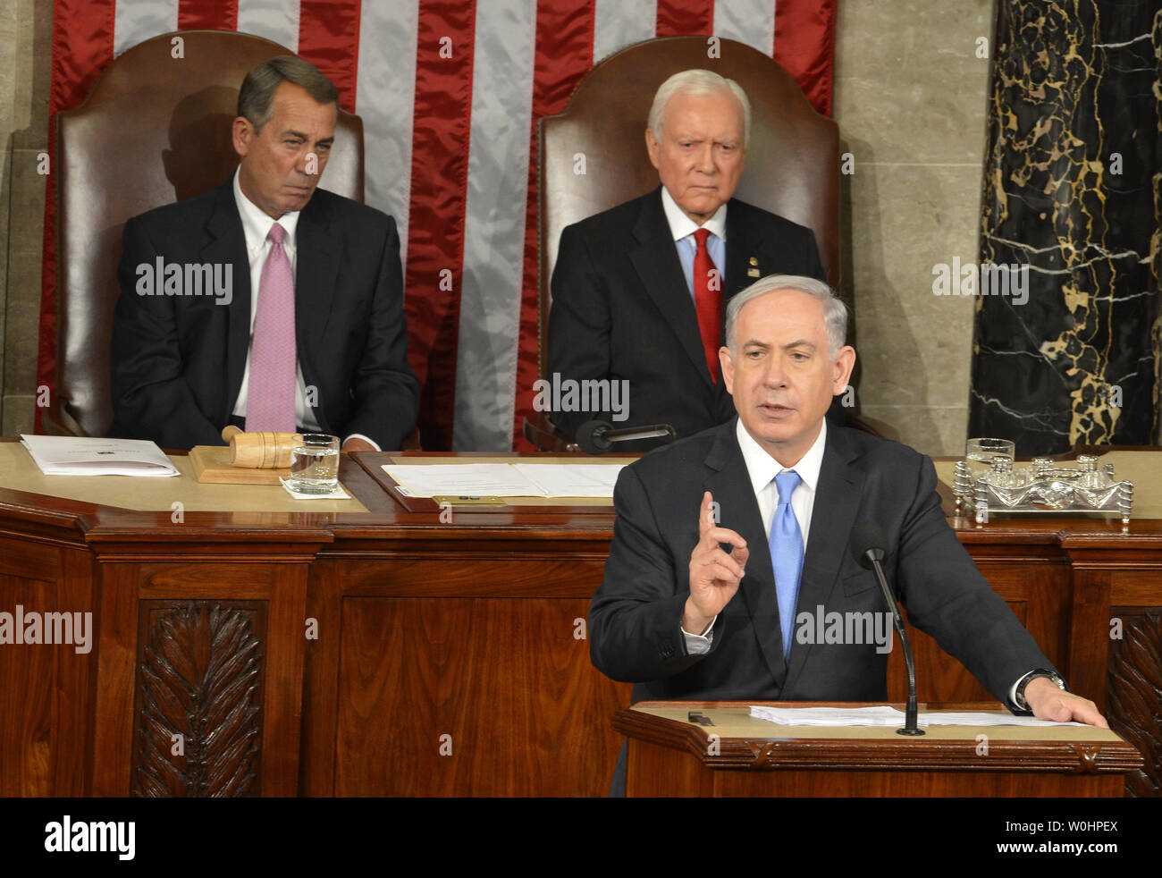 Israeli Prime Minister Benjamin Netanyahu addresses a joint meeting of Congress on nuclear talks with Iran, as House Speaker John Boehner (R-OH),(L), and Sen. Orrin Hatch (R-UT) listen, at the U.S. Capitol, March 3, 2015, in Washington, DC. The controversial speech, seen by many as interferring in American and Israeli politics prompted many congressmen to boycott the event.   UPI/Mike Theiler - Stock Image