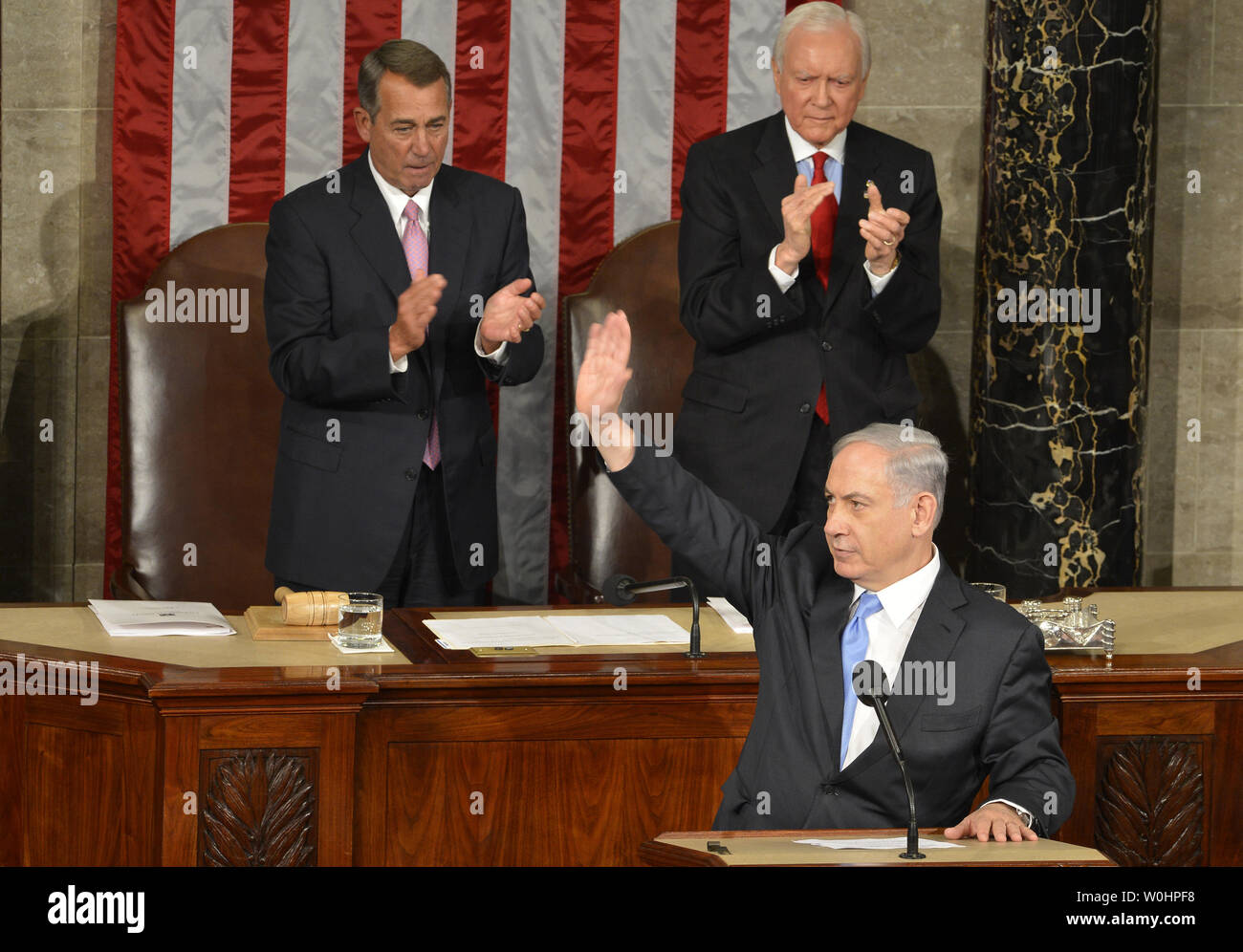 Israeli Prime Minister Benjamin Netanyahu waves at the conclusion of his address to a joint meeting of Congress on nuclear talks with Iran, as House Speaker John Boehner (R-OH),(L), and Sen. Orrin Hatch (R-UT) applaud, at the U.S. Capitol, March 3, 2015, in Washington, DC. The controversial speech, seen by many as interfering in American and Israeli politics prompted many congressmen to boycott the event.   UPI/Mike Theiler - Stock Image