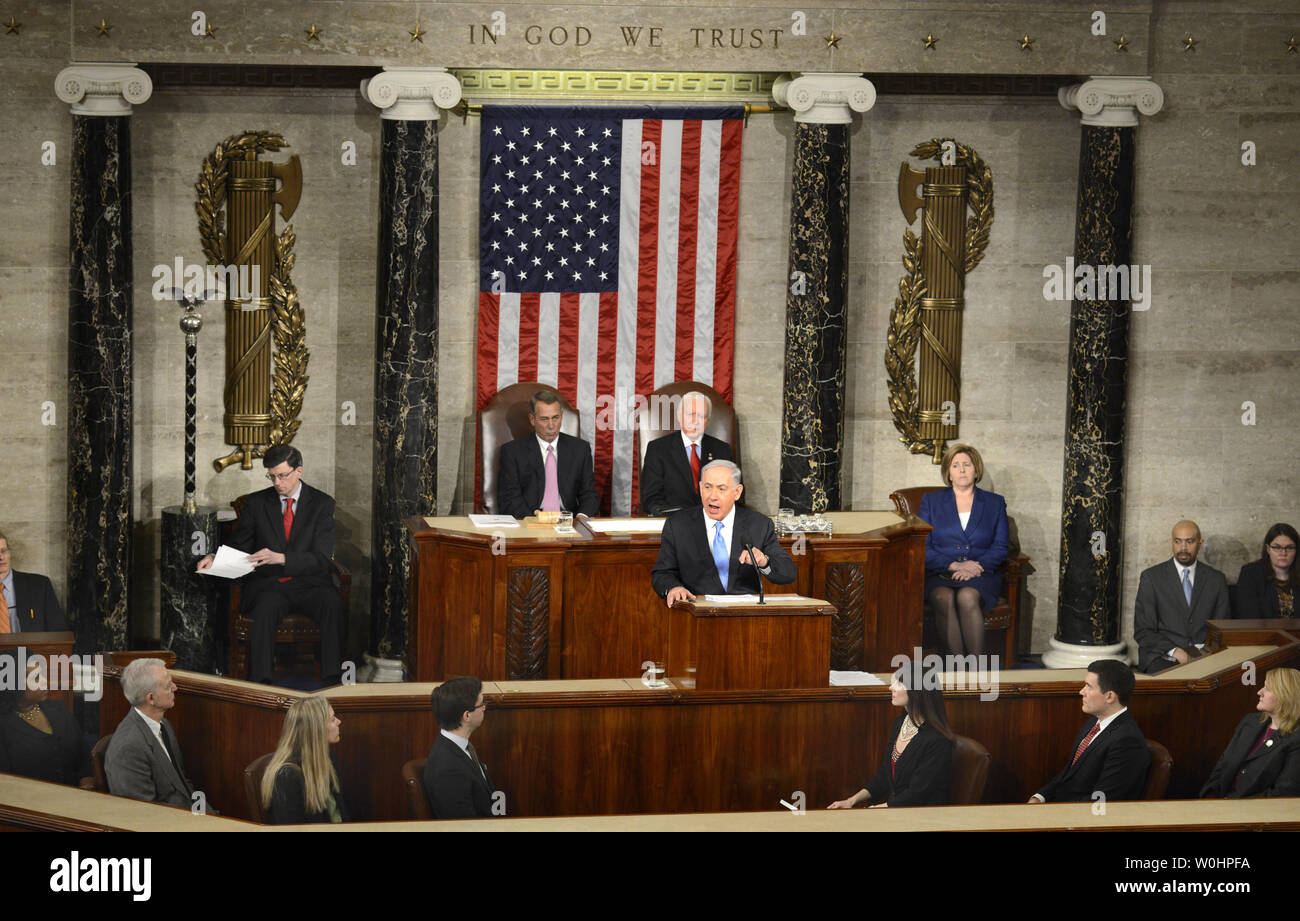 Israeli Prime Minister Benjamin Netanyahu (at the podium) addresses a joint meeting of Congress on nuclear talks with Iran, as House Speaker John Boehner (R-OH),(L), and Sen. Orrin Hatch (R-UT) listen, at the U.S. Capitol, March 3, 2015, in Washington, DC. The controversial speech, seen by many as interferring in American and Israeli politics prompted many congressmen to boycott the event.   UPI/Mike Theiler - Stock Image