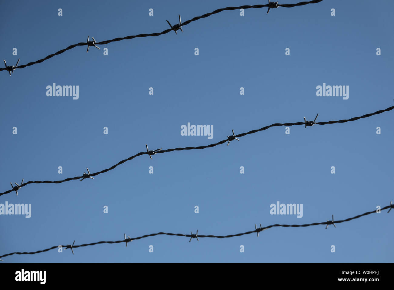 Three rows of rusty barbed wire in front of a blue sky, abstract Stock Photo