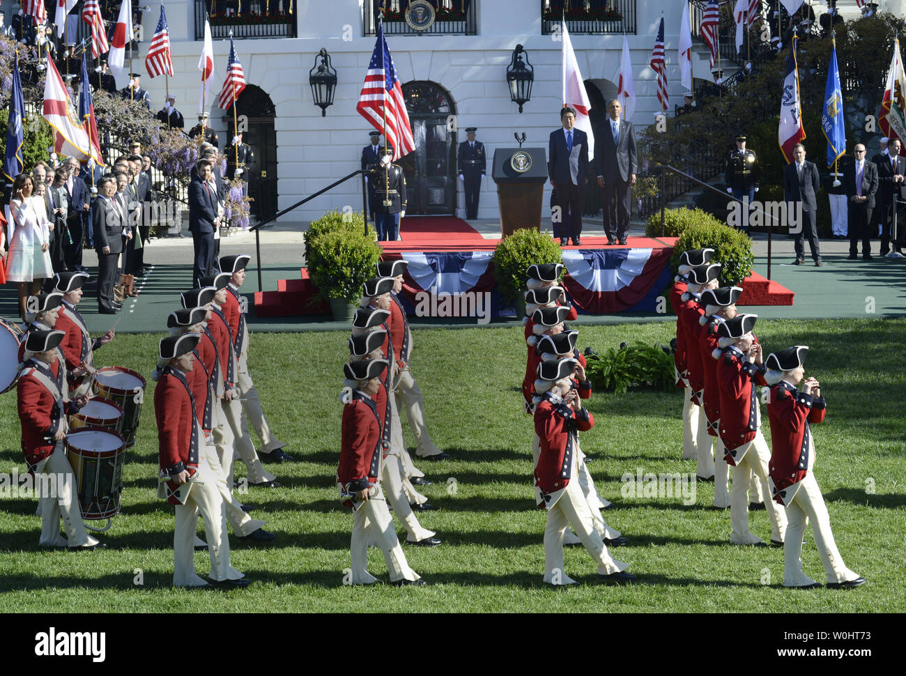 U.S. President Barack Obama and Japanese Prime Minister Shinzo Abe (on riser, background) watch as Colonial-era fife and bugle corps pass in review  during a welcoming ceremony on the South Lawn of the White House, April 28, 2015, in Washington, DC.        Photo by Mike Theiler/UPI - Stock Image