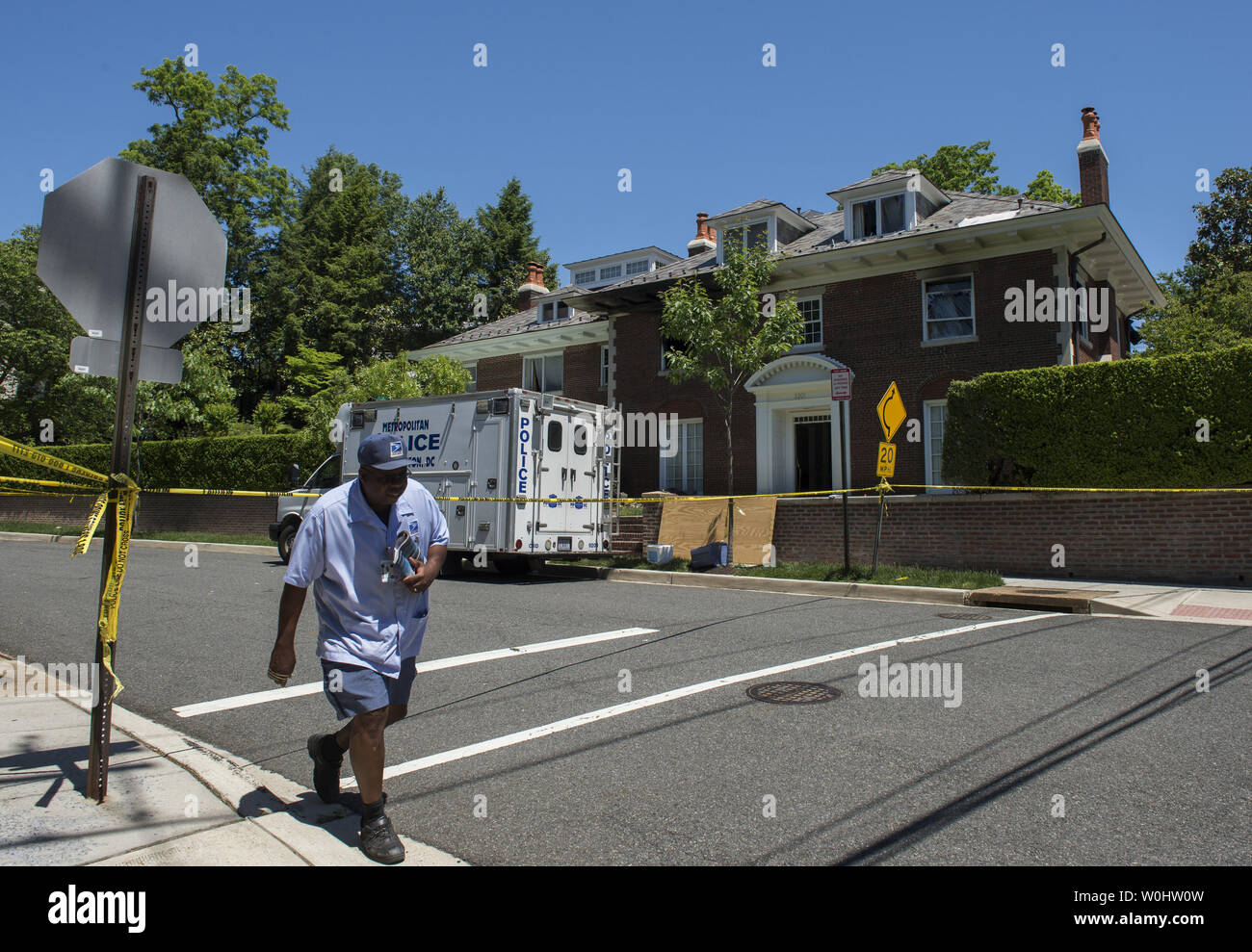 Mailman continues his route as police continue to inspect the $5 million house in the fashionable Northwest district of Washington, DC on May 23, 2015, where four people were brutally murdered after an apparent ransom was paid on May 14, 2015.  Police say captured suspect Daron Dylon Wint appeared to have accomplices in the murder of Savvas Savopoulos, his wife Amy, son Philip and housekeeper Veralicia Figueroa.  The lead on Wint apparently came from his DNA on a pizza crust.  Photo by Pat Benic/UPI - Stock Image