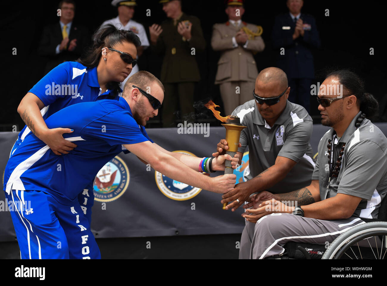 Air Force athlete Kevin O'Brien, held by escort Jennifer Stone, passes the torch to SOCOM athlete Sualauvi Tumalealiifano, right, with the help of escort Alfred D. Martinez, during the torch relay at the opening ceremony of the 2015 Department Of Defense Warrior Games at the United States Marine Corps base in Quantico, Va.,  June 19, 2015.  Photo by Molly Riley/UPI Stock Photo