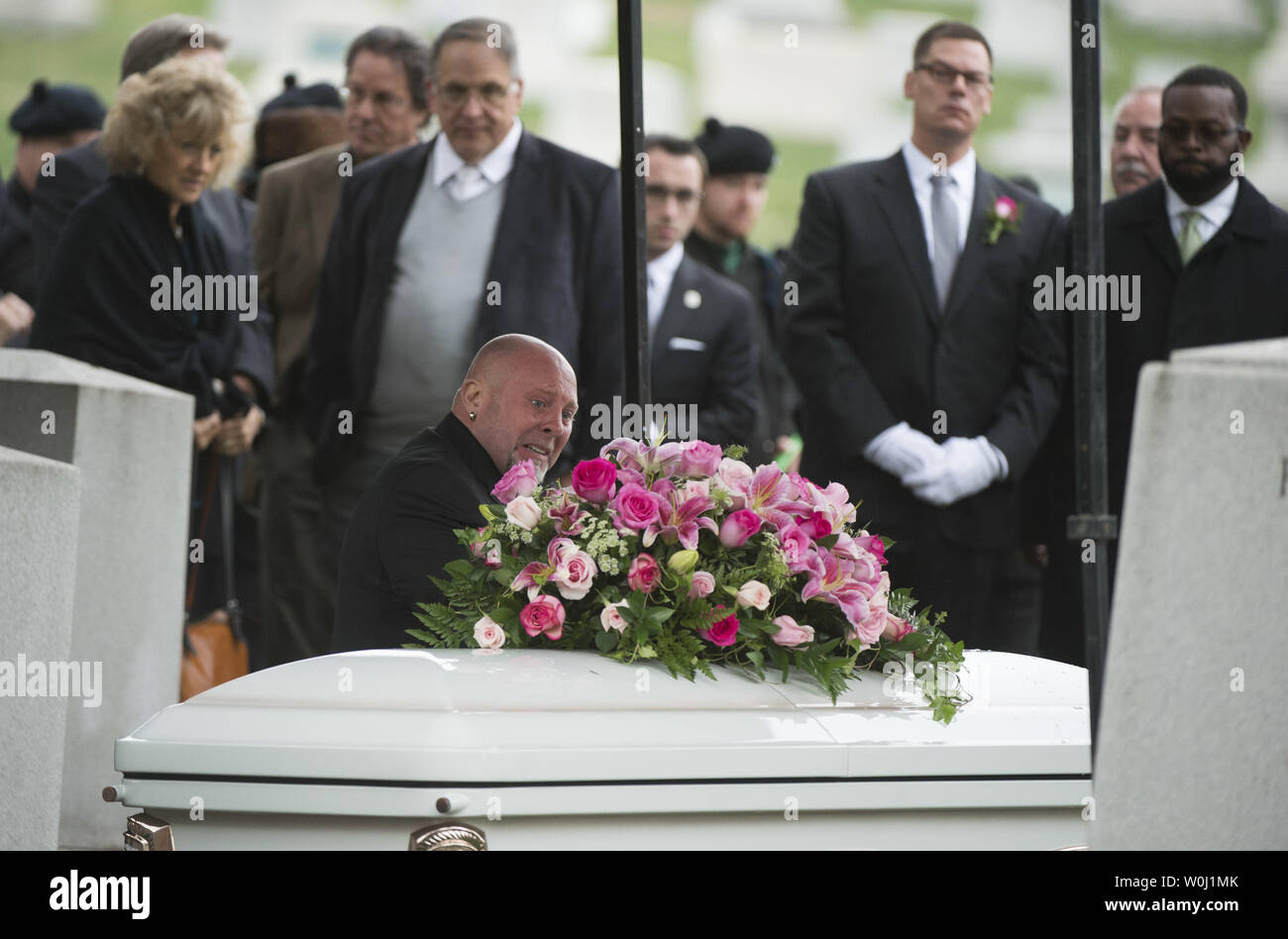 Conor FitzSimons, mourns at the grave of his grandmother actress Maureen O'Hara during her funeral, as she is buried to her husband Ret. U.S. Air Force Brig. Gen. Charles Blair, at Arlington National Cemetery in Arlington, Virginia on November 9, 2015. O'Hara, 95, starred in 'Miracle on 34th Street' and other classic hollywood films. Photo by Kevin Dietsch/UPI. - Stock Image