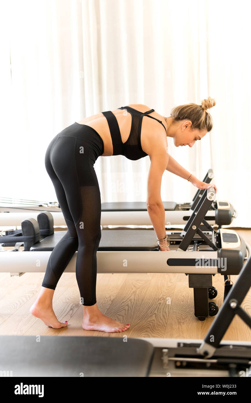 Woman in black workout clothes adjusting reformer bed in a pilates gym - Stock Image