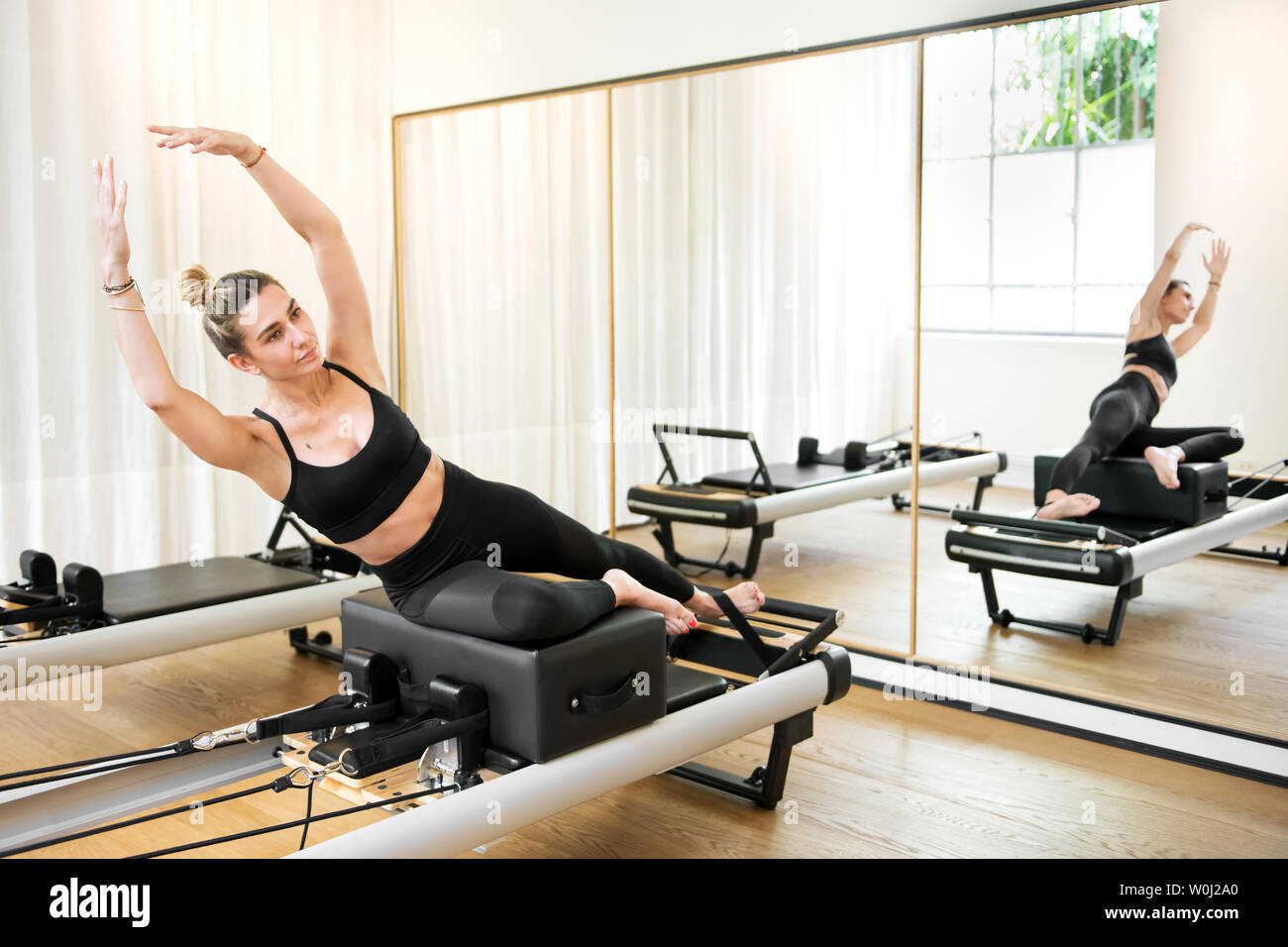 Woman making mermaid yoga exercise on reformer pilates bed reflecting in the mirror - Stock Image