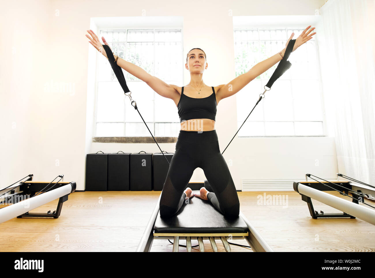 Single adult woman doing yoga arm work with straps exercise on reformer pilates bed - Stock Image