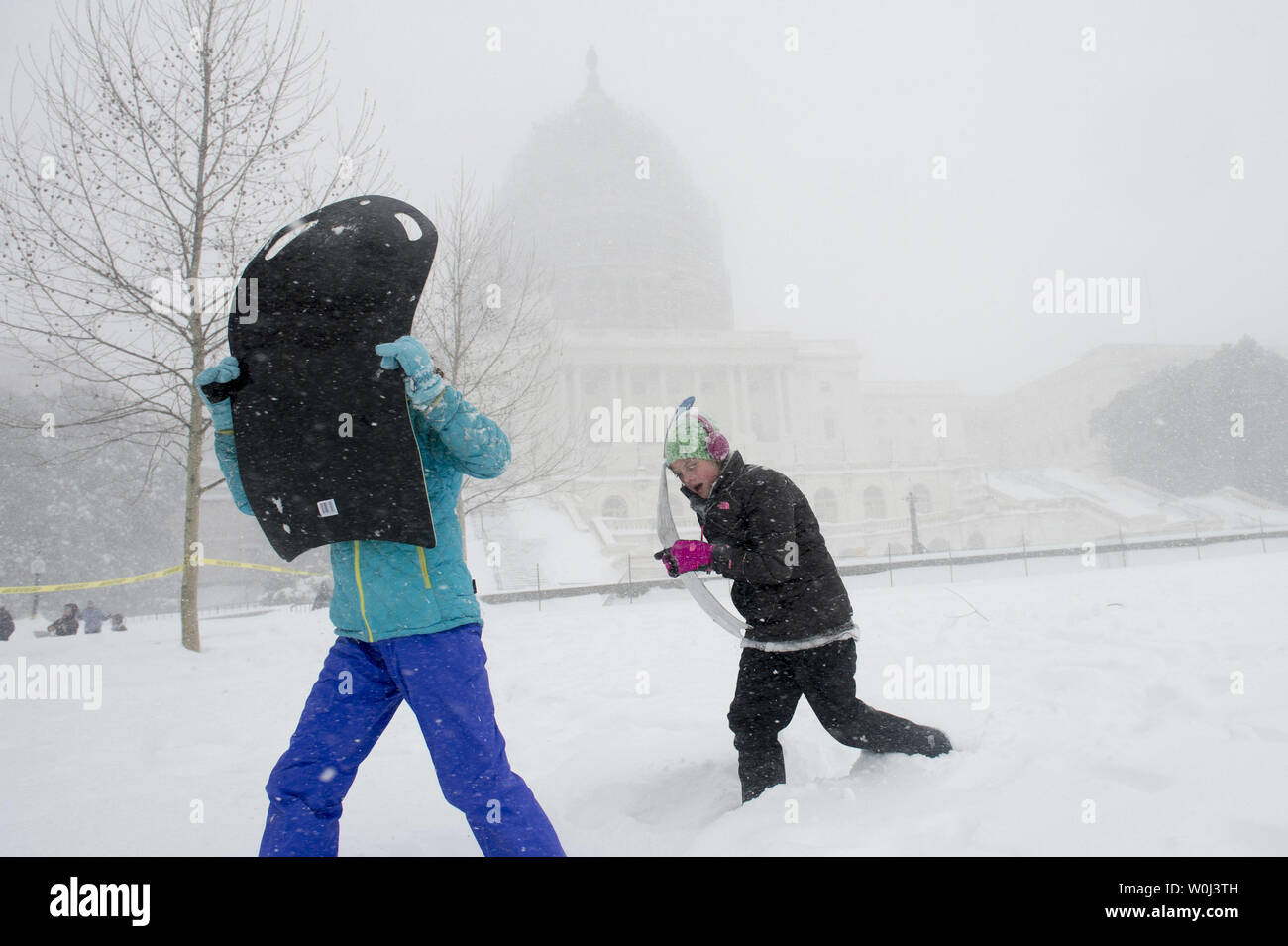 Two children use their sleds to shield themselves from strong winds as they walk near the U.S. Capitol Building in Washington, D.C. on January 23, 2016. A blizzard is hitting much of the East Coast dumping as much as 30 inches of snow and bringing white out conditions with winds topping 50 mph. Photo by Kevin Dietsch/UPI Stock Photo