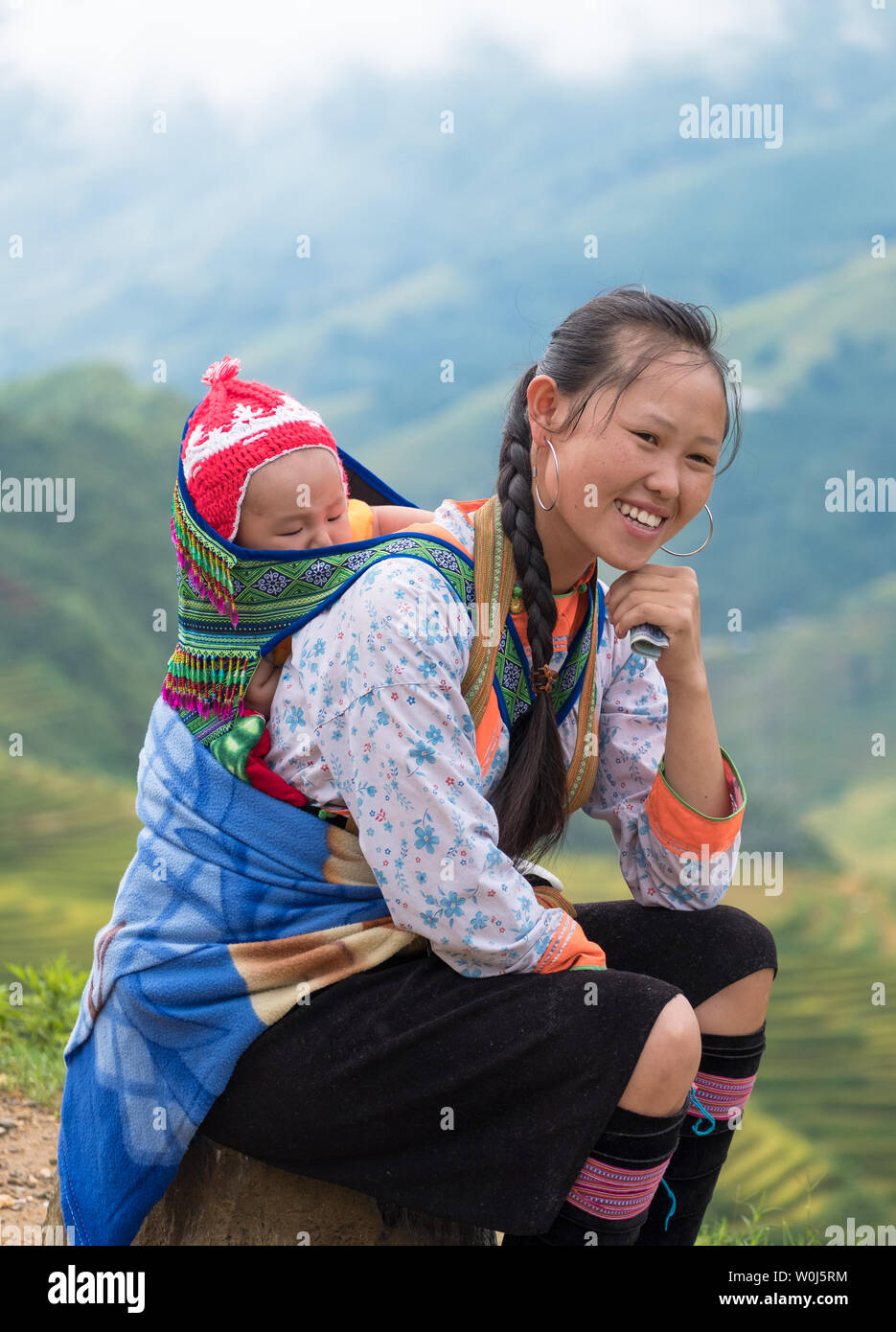 Sapa, Vietnam : Sep 08 2017 : Young mother tribe carrying son baby with smiling and happiness on rice field background - Stock Image