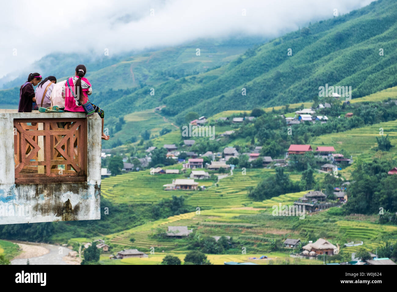 Sapa, Vietnam - Sep 08 2017 : Young girl tribe group sitting on terrace and view village on rice terraced in valley - Stock Image